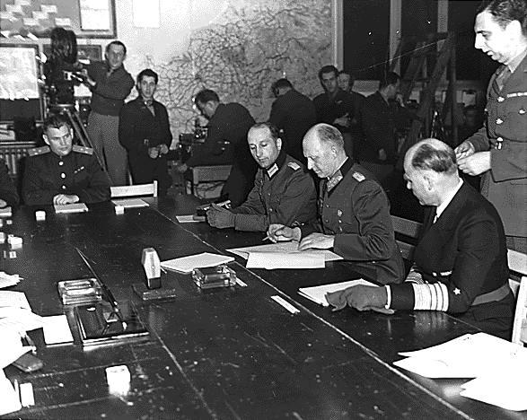 Il gen. Alfred Jodl firma la resa generale e incondizionata della Wehrmacht.