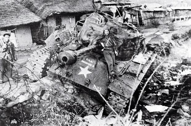 Soldati cinesi in posa su un carro americano distrutto.