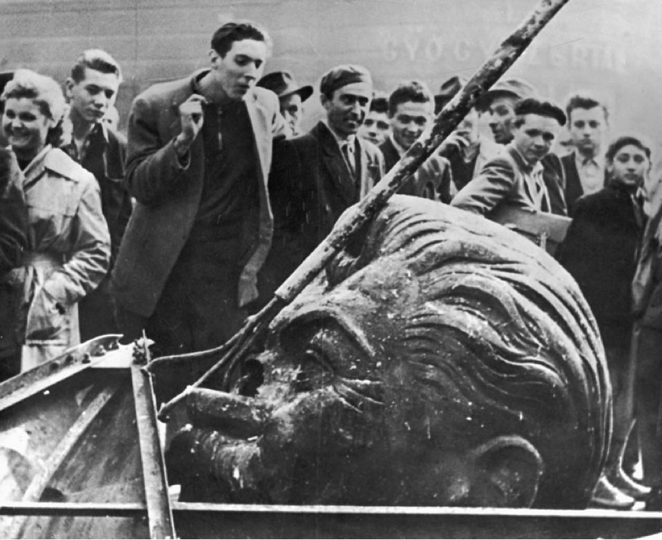Studenti sbeffeggiano una statua di Stalin appena abbattuta.
