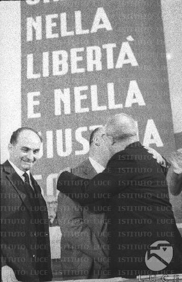 Saragat (a destra) abbraccia Reale sotto gli occhi di Tanassi sul palco del congresso PSDI.