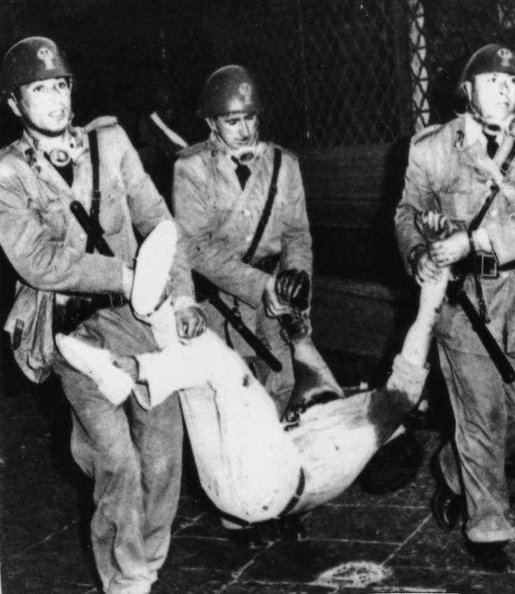 Poliziotti trasportano il corpo di Salvatore Novembre, ucciso negli scontri di Catania.