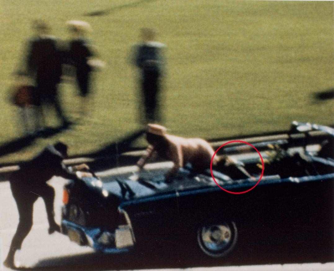 Un agente sale sull'auto presidenziale subito dopo l'uccisione di Kennedy che giace riverso (nel cerchio rosso).