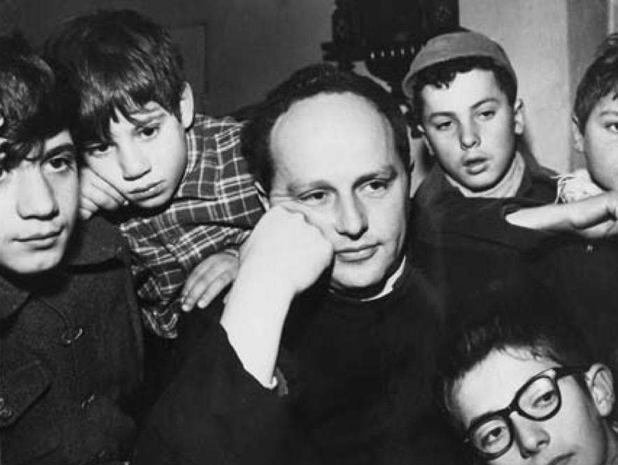 Don Milani con i ragazzi della scuola di Barbiana.