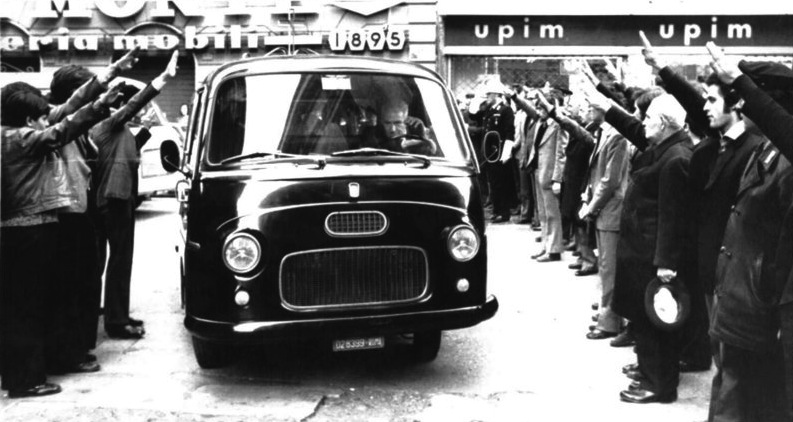 Militanti di destra eseguono il saluto fascista durante il trasporto delle vittime di Primavalle.