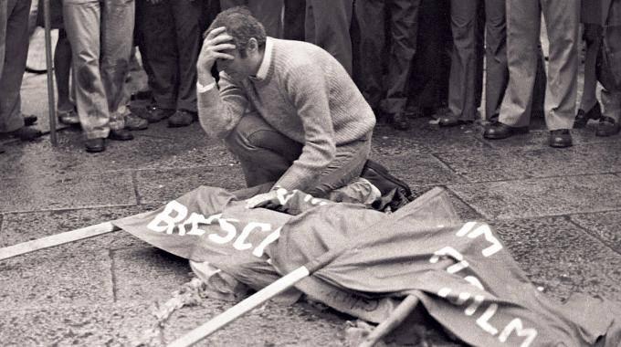 Il dramma di un congiunto davanti al corpo di una vittima della strage di Brescia.