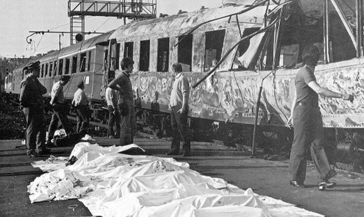 Le vittime della strage disposte davanti al treno Italicus, sventrato dalle bombe.