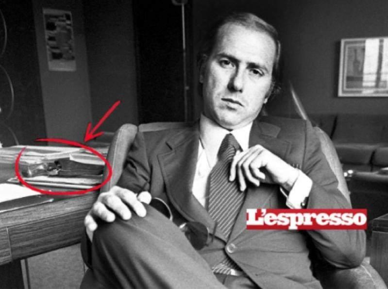 Foto dell'Espresso che mostra Berlusconi durante un'intervista, con una pistola sulla scrivania.
